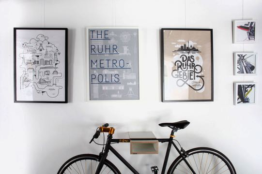 Three pictures in a frame on a wall, in front a bicycle.