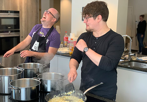 Two guys having fun while cooking breakfast.