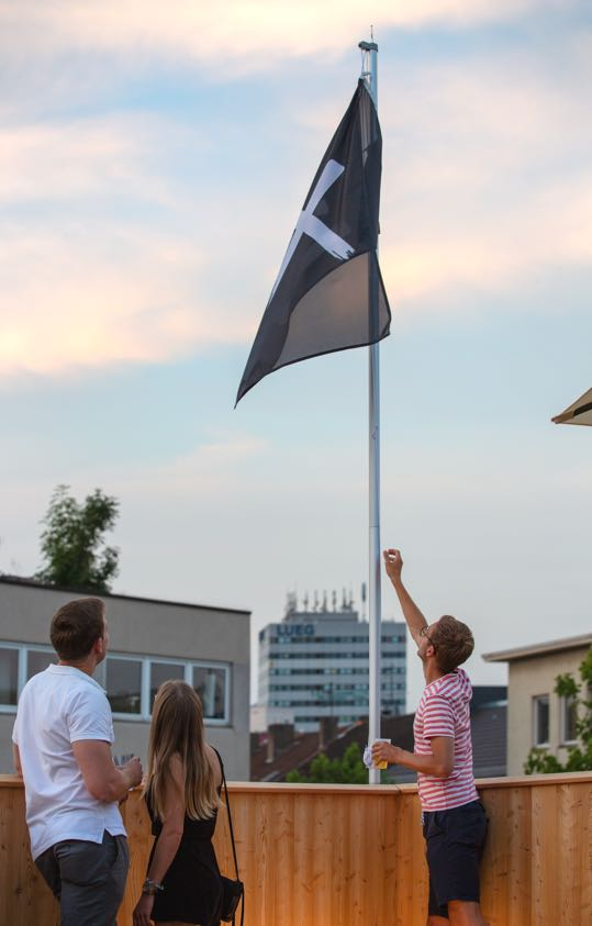Employees raising a flag showing the company logo